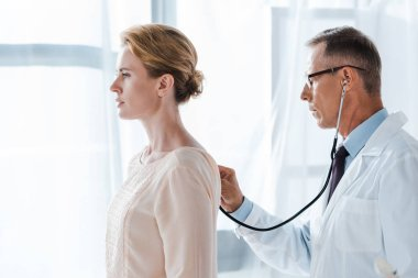 side view of doctor in glasses using stethoscope while examining attractive patient in clinic