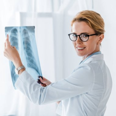 Beautiful and cheerful doctor in glasses looking at camera and holding x-ray in clinic stock vector