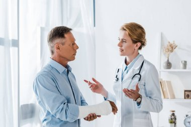attractive doctor gesturing near handsome man with broken arm in clinic