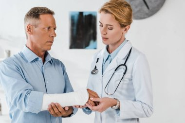 attractive doctor looking at broken arm on handsome man in clinic