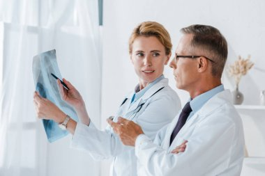 attractive doctor holding pen and x-ray near coworker gesturing in clinic