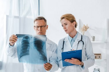 Attractive doctor holding clipboard and looking at x-ray near coworker stock vector