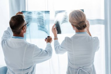 doctor in glasses and coworker standing and looking at x-rays in clinic