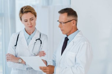 man in glasses and white coat looking at blank paper near coworker with crossed arms