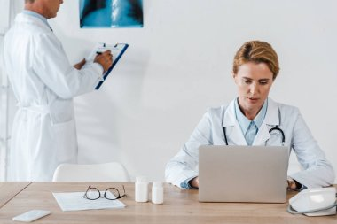 cropped view of doctor standing near x-ray and attractive colleague using laptop