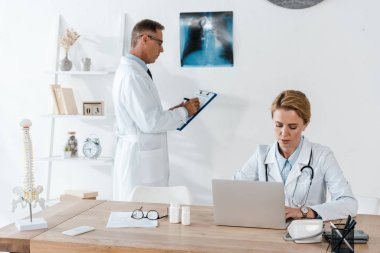 handsome doctor standing near x-ray and attractive colleague using laptop