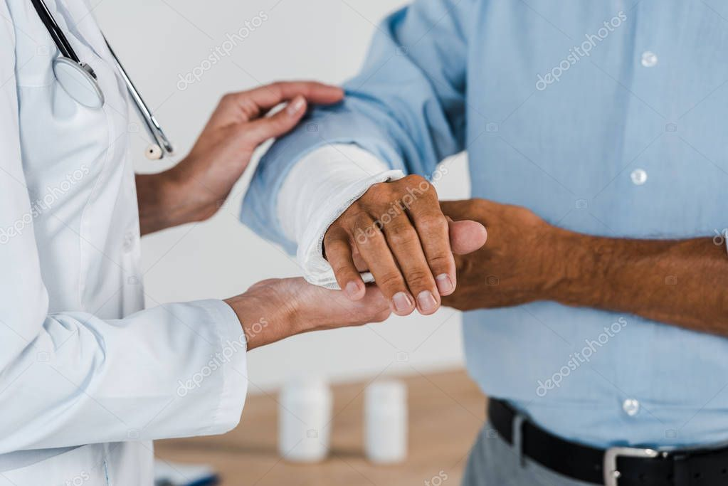 Cropped view of doctor touching broken arm on man in clinic stock vector
