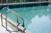 transparentní plavecký bazén s zábradáči na letovisku během dne
