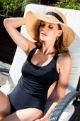 beautiful girl in swimming suit and straw hat resting on sun bed on resort