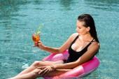 szép lány koktéllal az úszás Ring az uszodában a Resort
