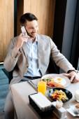 usměvavý obchodník sedí na servírovacím stole a mluví na smartphone v kavárně