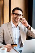 mosolygó üzletember a szemüveg beszél okostelefon és a gazdaság hitelkártya asztalnál laptop a kávézóban