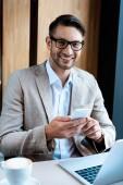 usmívající se obchodník v brýlích, které drží smartphone a sedí u stolu s notebookem v kavárně