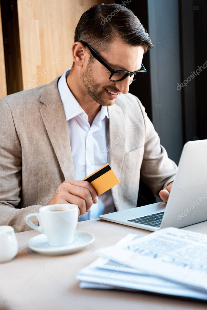 Smiling businessman in glasses with credit card and laptop in cafe stock vector