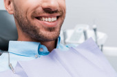 cropped view of happy patient smiling in dental clinic