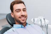 Veselý vousatý muž s úsměvem a pohledem na kameru na zubní klinice