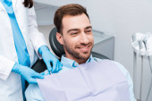 abgeschnittene Ansicht des Zahnarztes in blauen Latexhandschuhen stehen in der Nähe von fröhlichen Patienten