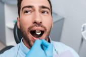 cropped view of dentist holding dental mirror in mouth of handsome patient