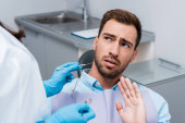 selective focus of bearded patient gesturing near woman holding dental instruments