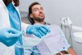 abgeschnittene Ansicht des Zahnarztes hält medizinische Maske in der Nähe von Patienten in zahnärztlicheklinik
