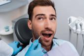 Fotografia vista ritagliata del dentista tenendo strumento dentale vicino uomo bello