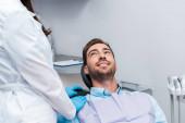 abgeschnittene Ansicht des Zahnarztes in weißem Mantel steht in der Nähe von fröhlichen Mann in Klinik