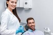 Fotografie attractive and happy dentist holding dental equipment near happy man