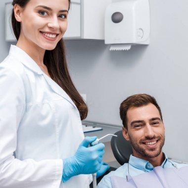 beautiful and happy dentist holding dental equipment near happy man