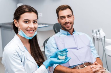 selective focus of attractive dentist in latex gloves holding teeth model near patient with clenched hands