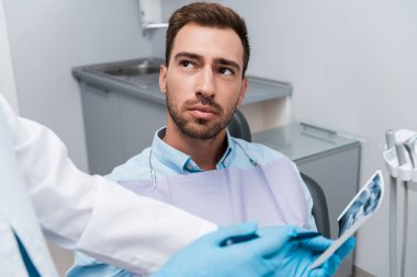 cropped view of dentist holding x-ray near handsome patient