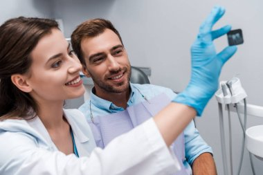 selective focus of attractive dentist and smiling patient looking at x-ray
