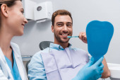 Fotografie selective focus of happy man brushing teeth near attractive dentist holding mirror