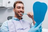 Fotografie oříznutý pohled na zubaře přidržel zrcadlo poblíž veselý člověk kartáčováním zubů
