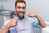 handsome bearded man showing thumb up while holding toothbrush