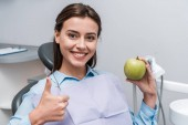 cheerful woman holding green and tasty apple while showing thumb up