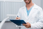 cropped view of happy bearded doctor holding clipboard and pen in clinic