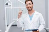 šťastný vousatý doktor v brýlích přidržujícími schránku a pero při ukazování prstem na klinice