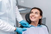cropped view of dentist in latex gloves near cheerful woman