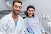 selektivní zaměření šťastné a přitažlivé dívky usmívající se u hezkého zubaře v brýlích