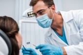 selective focus of dentist in medical mask holding dental instruments near patient