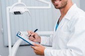 cropped view of bearded man in white coat holding pen and clipboard in dental clinic