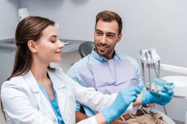 selective focus of man looking at cheerful dentist holding toothbrush near teeth model