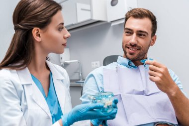 selective focus of handsome man holding retainer near dentist with teeth model in hands