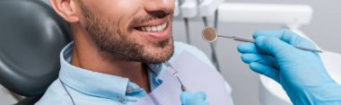 panoramic shot of dentist in latex gloves holding dental instruments near patient