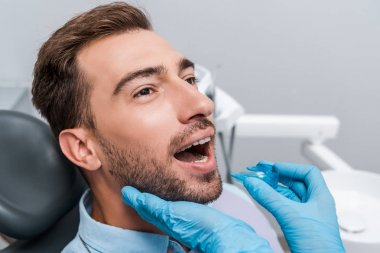 cropped view of dentist in blue latex gloves holding retainer near bearded man