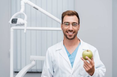 Happy bearded doctor in glasses holding green and tasty apple stock vector