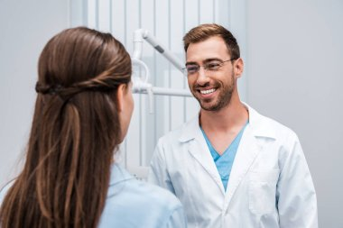 selective focus of cheerful dentist in glasses looking at patient in clinic