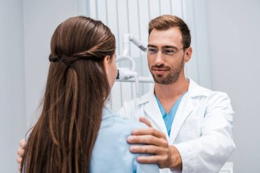 selective focus of cheerful dentist in glasses touching shoulders of patient in clinic