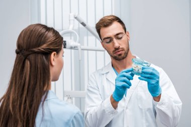 selective focus of bearded dentist in glasses holding tooth model near patient