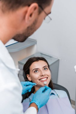 selective focus of man in latex gloves holding dental instruments near attractive woman